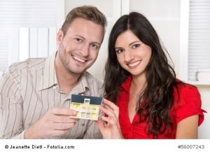 Junges lachendes Paar kauft eine Immobilie - ein Eigenheim